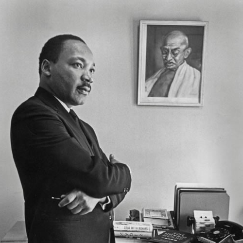 Martin Luther King Jr. standing in front of an image of Mahatma Gandhi. Image courtesy of Stanford University Libraries, Bob Fitch Photography Archive Permission: //exhibits.stanford.edu/fitch/catalog/zm389mc0116